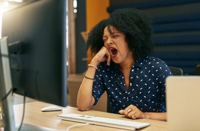 1572384716553_tired-woman-in-office-yawning-at-desk-after-eating.jpg